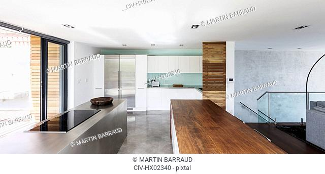 Modern, minimalist home showcase interior kitchen with wood and stainless steel counters