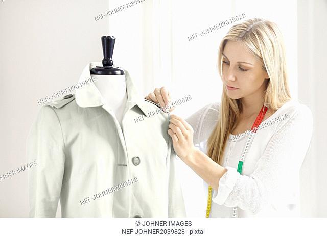 Woman preparing coat on mannequin
