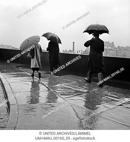 Menschen an einem Regentag unterwegs mit ihren Regenschirmen, Deutschland 1930er Jahre. People on a rainy day on their way with their umbrellas, Germany 1930s