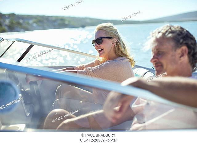 Couple driving boat in water