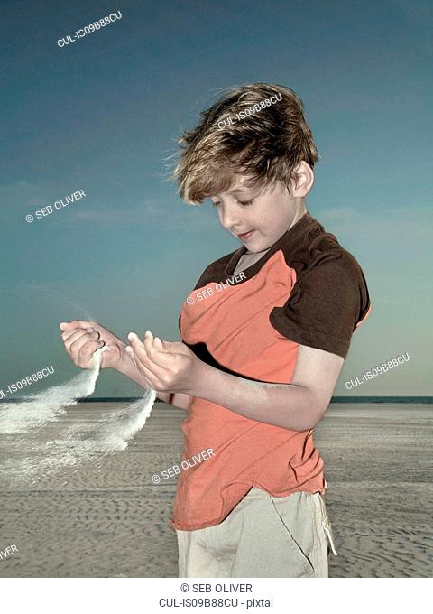 Boy gazing at sand blowing from hands on beach, Miami, Florida, USA