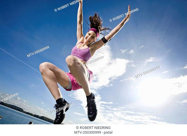 Woman jumping on jetty, Woerthsee, Bavaria, Germany