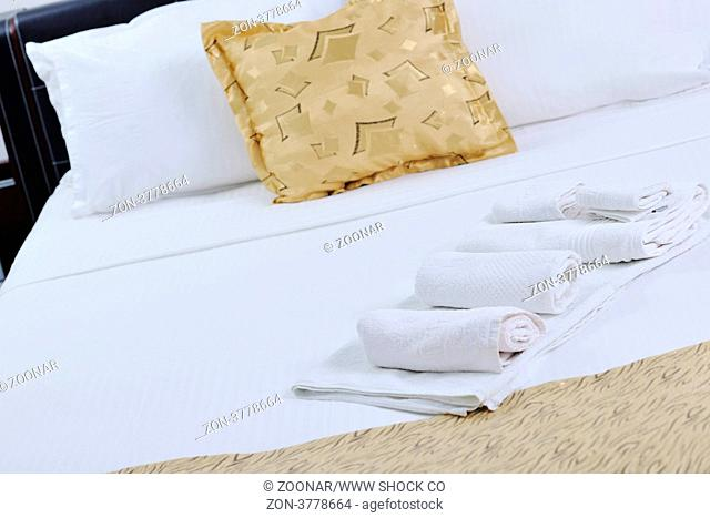 white towels on bed in luxury hotel room with yellow pillow in background