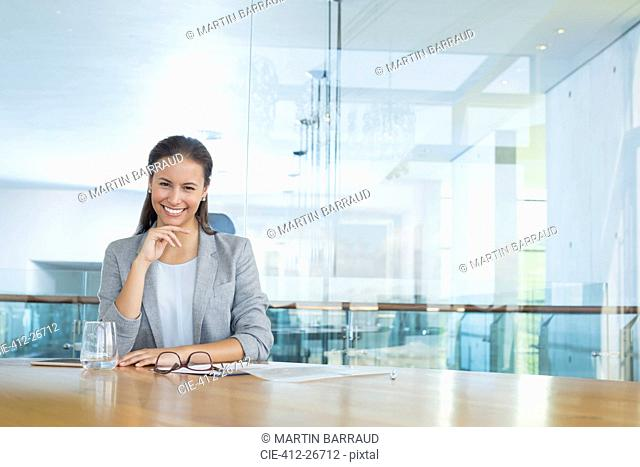Portrait confident businesswoman at conference room table