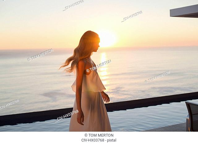 Woman in white dress on tranquil luxury patio with sunset ocean view