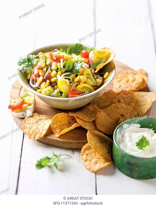 A bowl of spicy sweetcorn and tomato salsa with tortilla chips