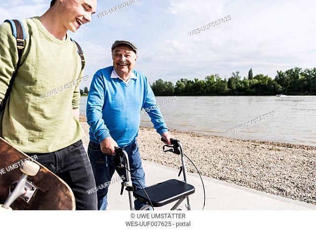 Grandfather and grandson strolling together at riverside