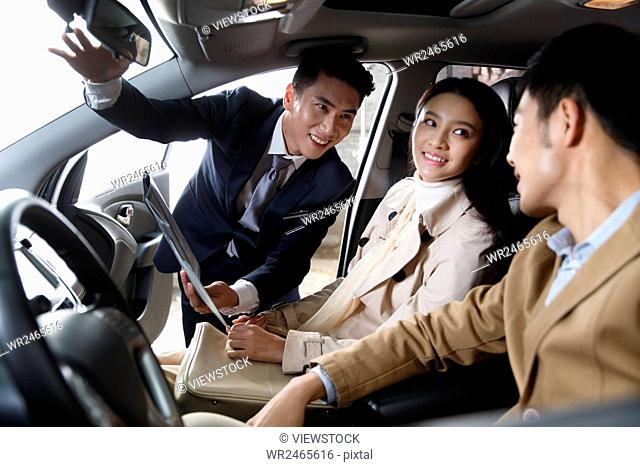 Car salesman talking to couple