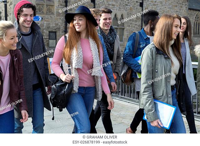 A group of happy young students smile as they walk through the city together on a break from university. They are carrying their bags, books and digital tablets
