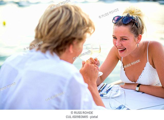 Young couple laughing at waterfront restaurant, Majorca, Spain