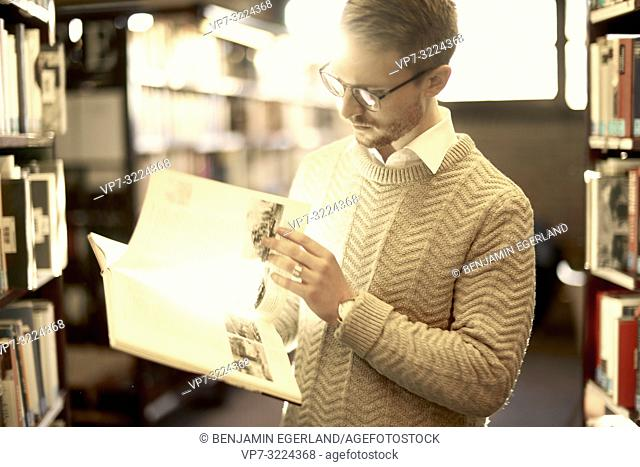 man browsing book, library, glasses, student, university, knowledge