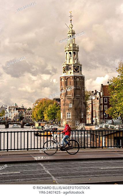 Bicyclist crossing Prins Hendrikkade at the Montelbaanstoren Tower in Amsterdam