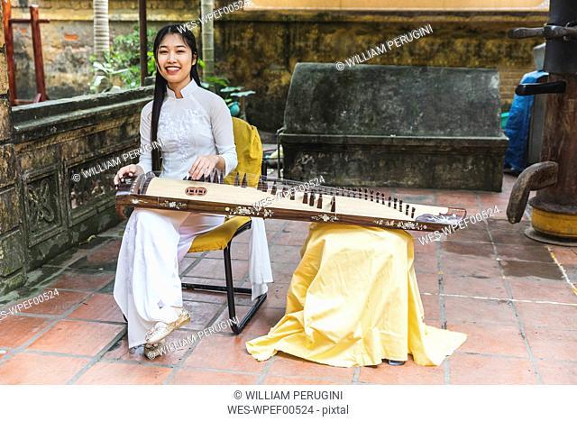 Vietnam, Hanoi, young woman with Dan tranh