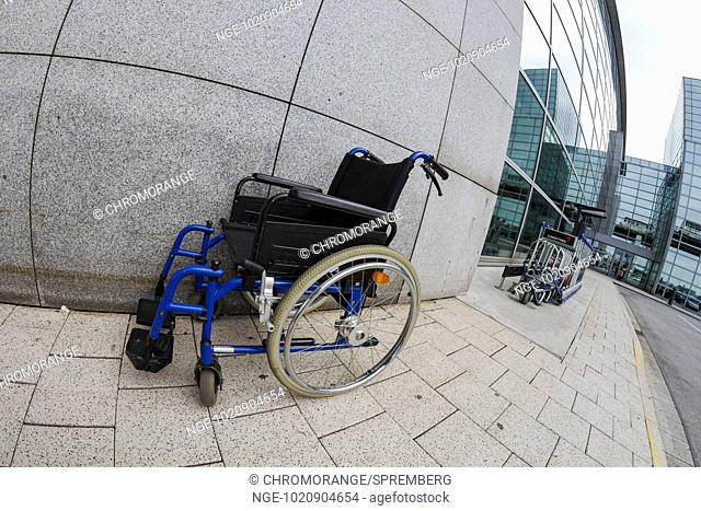 abandoned wheelchair standing in front of a house wall
