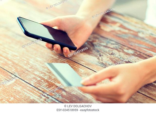 business, technology, cash free and internet people concept - close up of male hands holding smart phone and credit card on wooden table