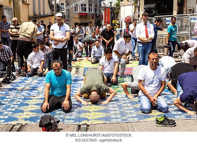 Muslims praying during Friday prayers in a street near Taksim Square, Istanbul, Turkey