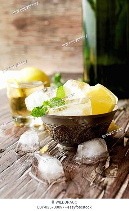 Glass of whiskey with mint and lemon with ice cubes wooden table, or tea, selective focus