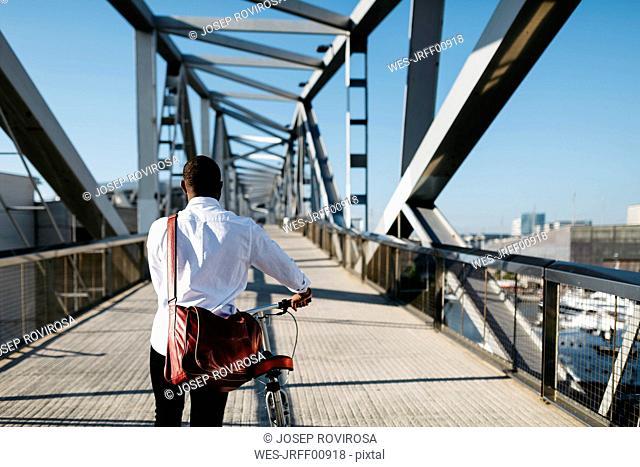 Man pushing bicycle on a bridge
