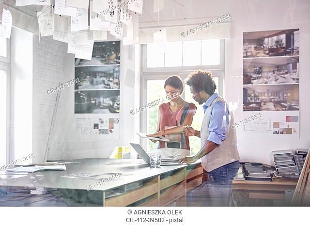 Design professionals using digital tablet, brainstorming in office