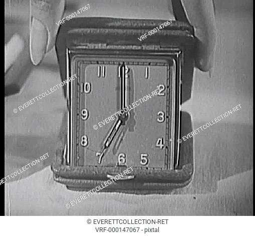 Close-up of woman's fingers turning alarm clock