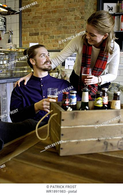 Young couple drinking beer, crate with various brands in foreground, Dorset, Bournemouth, England