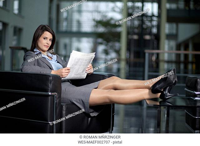 Germany, Bavaria, Business woman with newspaper, smiling, portrait