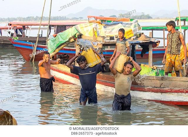 Myanmar, Rakhine state, Mrauk-U, men unload by hand boats loaded with stones