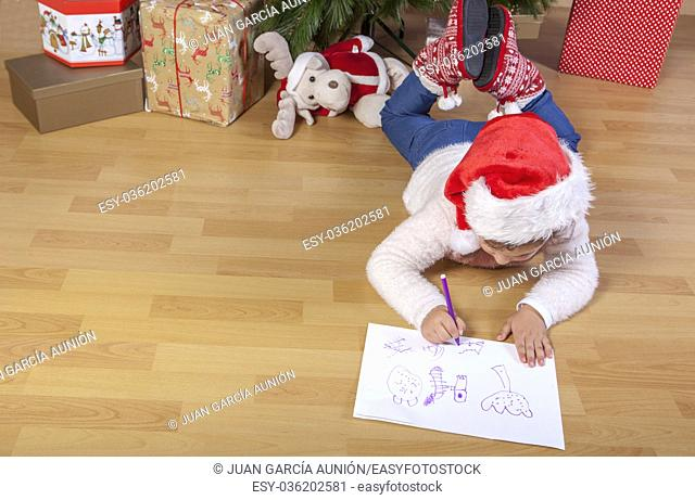 Little girl preparing the Santa Letter. She painting the gifts she want. Pre-reader concept