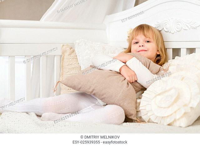 Happy pretty girl embracing pillow sits on a sofa in the room