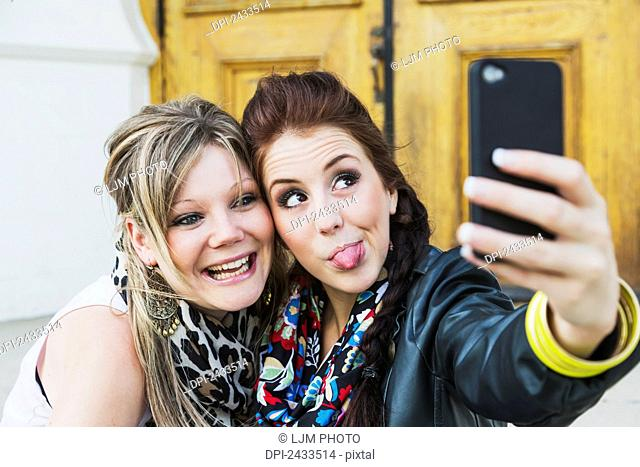 Two friends taking a self-portrait with a cell phone; Edmonton, Alberta, Canada