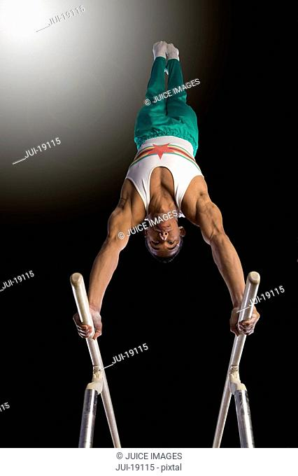 Male gymnast performing handstand on parallel bars, low angle view