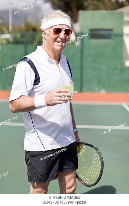 Older man drinking lemonade on court