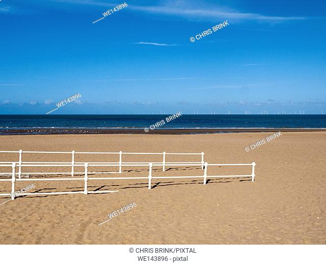 Entrance to the sandy beach with windfarm in distance, Colwyn Bay, North Wales, UK