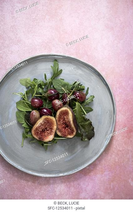 A salad with figs, garpes and lettuce on a grey plate on a pink backdrop