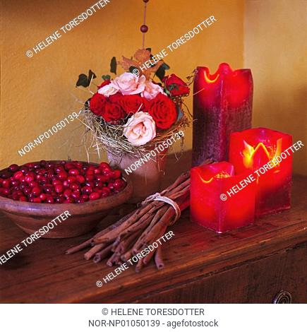 Roses in a vase with red berries and candle frames