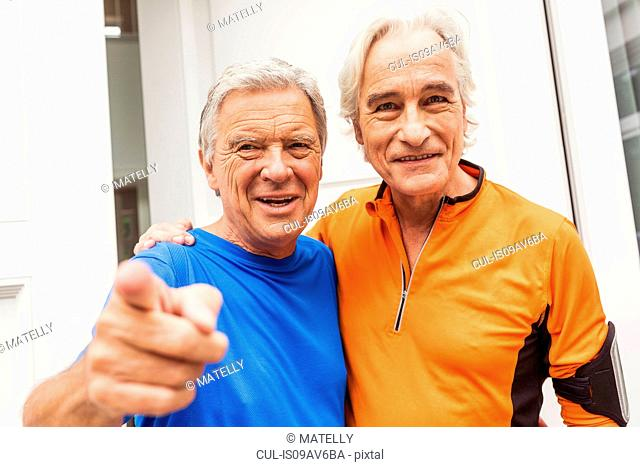 Portrait of two happy senior male runners at front door