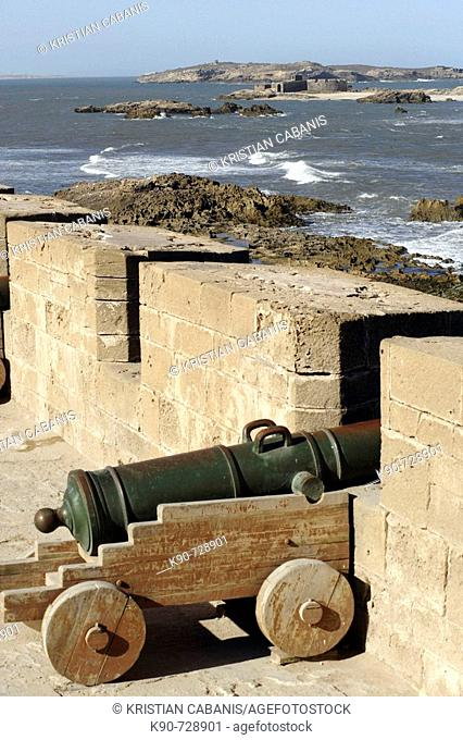 Portugese bronze cannon defending the crenellated wall of the Kasba Sqala of Essaouira with islands and the Atlantic Ocean in the background