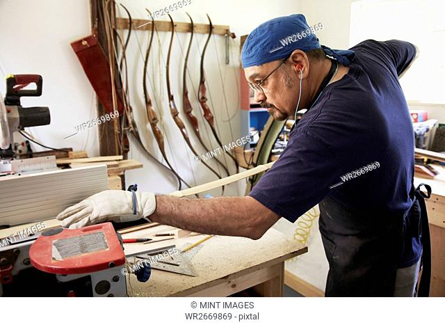 A bow maker working on a wooden bow in his workshop