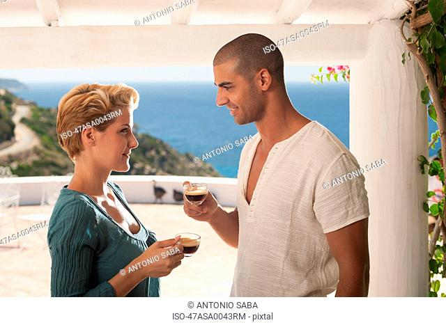 Couple drinking coffee on balcony
