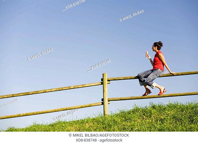 Portrait of a young woman sitting on a fence eating a ice cream