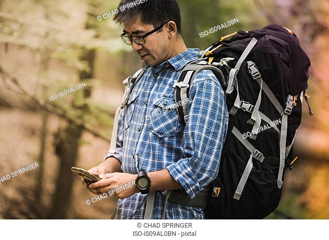 Hiker with backpack, looking at smartphone
