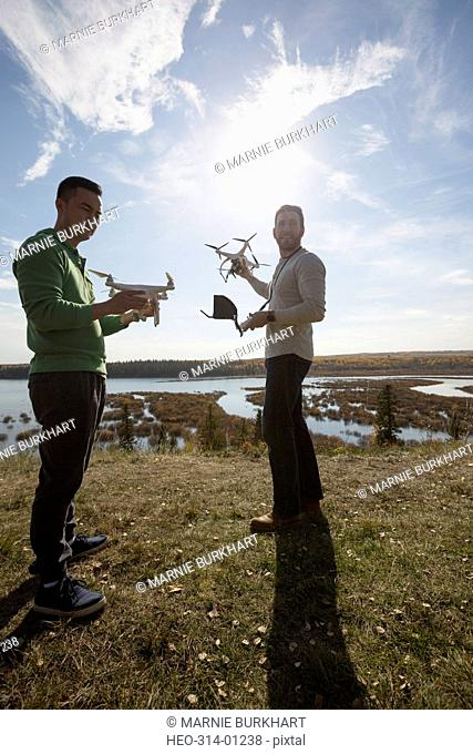 Male friends with drone equipment on sunny hilltop overlooking lake