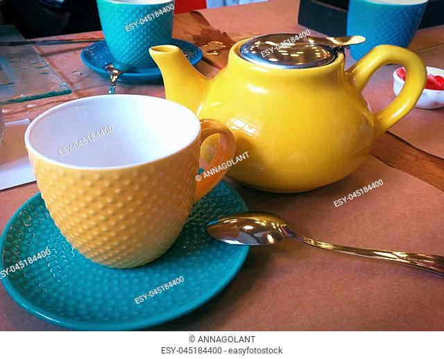 Breakfast in the cafe. Teapot, Cup and saucer. Bright, colorful colors. Close-up photo