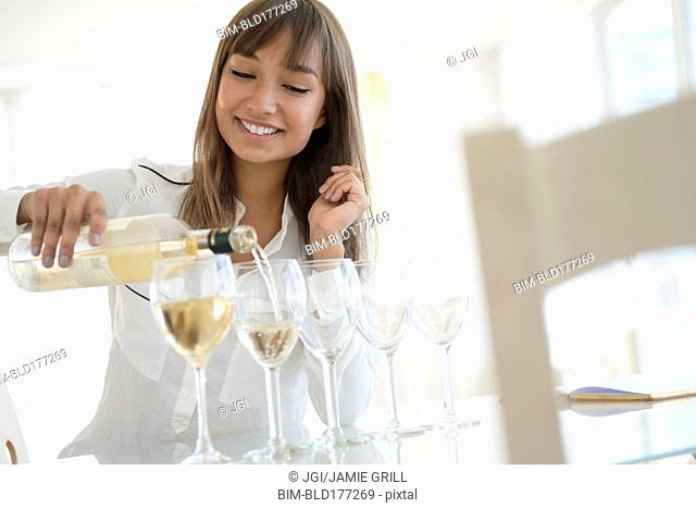Mixed race woman pouring white wine