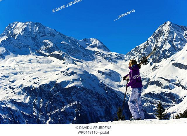 A skier looks at the mountains and glaciers