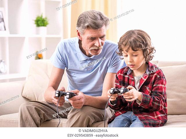 Grandfather and grandson are playing video games at home