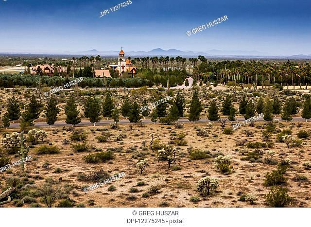 Church steeple with cross and trees and plants on arid landscape; Phoenix, Arizona, United States of America