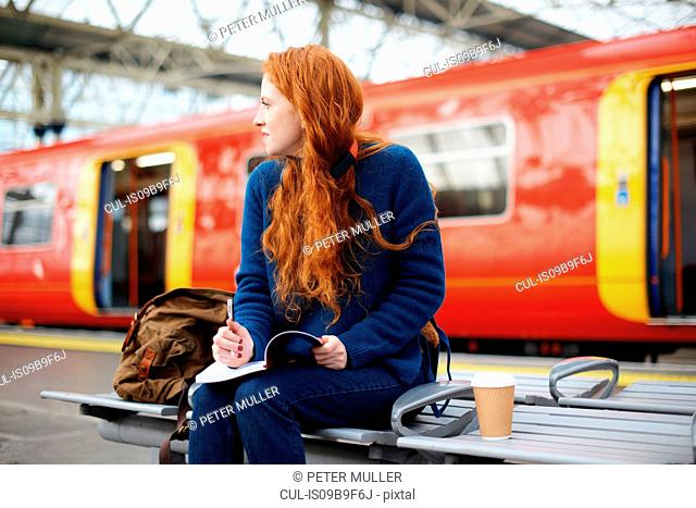 Woman on bench on train station platform, London