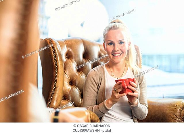 Mid adult woman sitting in leather armchair holding coffee cups looking at camera smiling