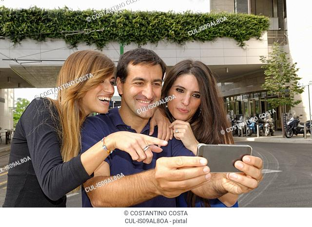 Three friends looking at smartphone